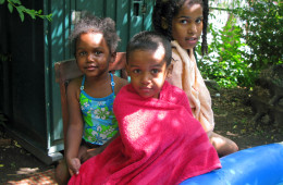 Garden members' children dry off after swimming in an inflatable pool.
