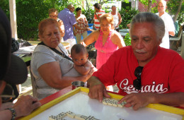 Jorge Torres and family and friends playing dominoes in the garden where he grows cane.